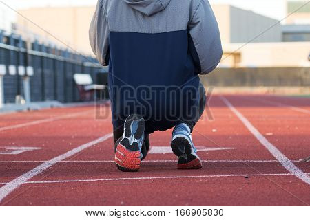 An athlete kneeling as she gets ready to start a 100 meter sprint during track and field training in the winter