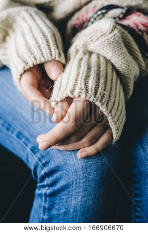 Girl's hands in casual wool sweater on her knees on denim jeans. Warmth and comfort concept. Winter mood.