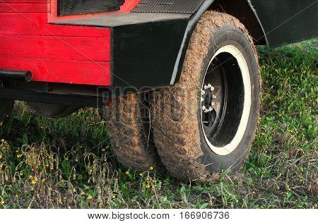 Muddy dual wheel retro truck closeup in a countryside
