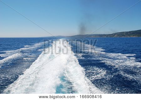 The wake from the stern of a high speed hydrofoil ferry departing from the Greek island of Paxos.