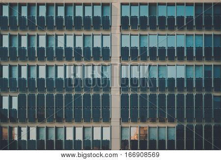 Facade of modern contemporary dark teal office building with a lot of photovoltaic plates on it multiple sun plates on house regular rows of solar batteries in front of windows on daytime