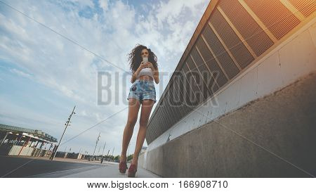 Young curly hipster brunette girl read text message on her cell telephone while standing on the street pretty woman with long legs chatting on smart phone with friend during walking in urban settings