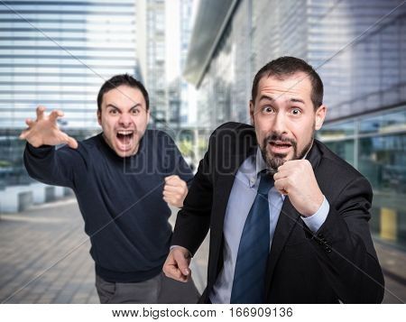 Businessman running away from an angry customer