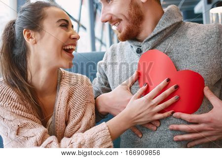 man and woman smiling and holding a large paper heart. Two people, man and woman in cafe communicate, laughing and enjoying the time spending with each other. Couple in love on a date. Love story and Valentines Day concept