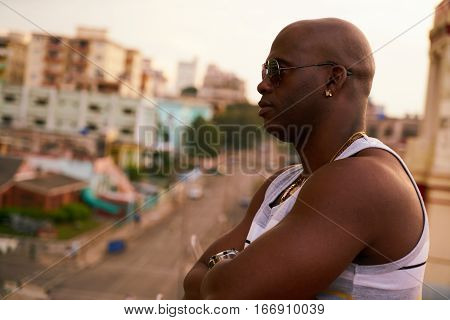 Black gang member with arms crossed contemplating cityscape at sunset.