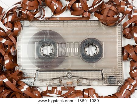 Vintage transparent Compact Cassette with pulled out tape audio background
