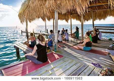 CAYE CAULKER, BELIZE - DEC 17 2015: Yoga at dock of Caye Caulker island on Dec 17, 2015, Belize. Participants perform yoga moves outdoors by the sea.