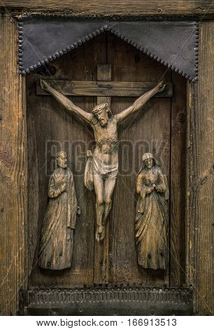 Crucifixion of Christ carved on ancient wooden icon. The wooden figure of the Crucifixion of Christ. Old wooden icon of the Crucifixion of Christ with a close-up. Cracked figurine on the icon.