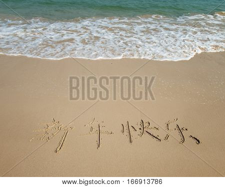Chinese Calligraphy for happy new year written in the sand