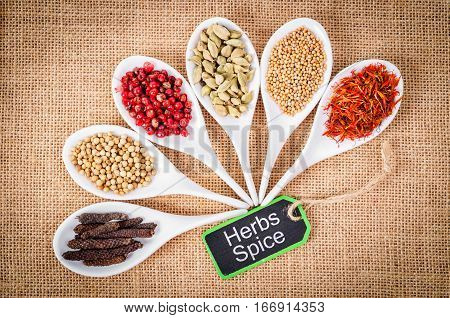 various spices and herbs with herbs spices wooden tag on sack background.