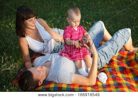 Young beautiful couple lying on the grass in park with their one year old daughter and having fun