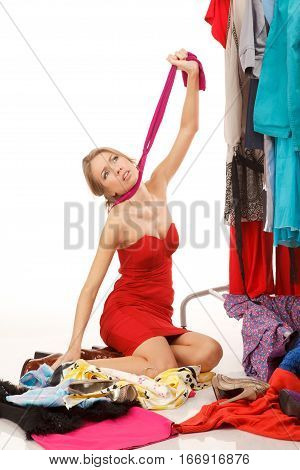 Young woman sits near her clothes rack with lots of dressesand some clothes is on the floorand she is choking her self with her pantyhose