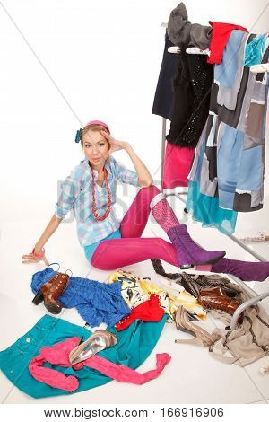 Young woman sits near her clothes rack with lots of dressesand some clothes is on the floor
