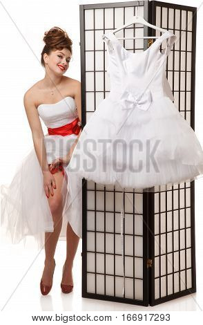 Pin-up bride standing near folding screen with another wedding dress hanging on it.Professional make-up hair and style