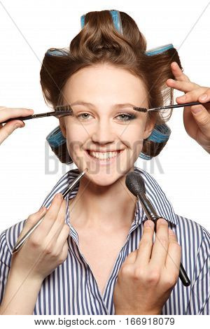 Young woman in curler in her hair and one eye with make-upshe is expressing her emotions. With multiple hands applying make up.