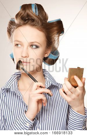 Young woman in curler in her hair and one eye with make-upshe is applying make up.