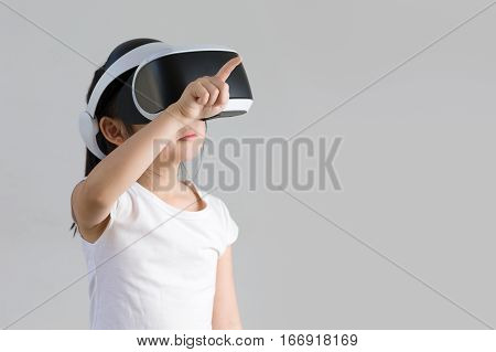 Studio shot of child with virtual reality VR headset isolated on white background. Kid wearing VR goggles to explore digital virtual world.