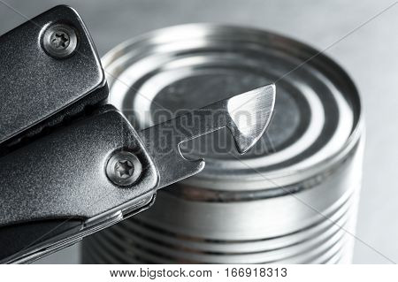 opening the tin with tin opener (can opener)