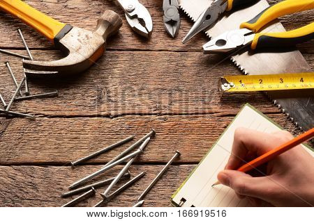 A top view image of various hand tools on a wooden work bench.