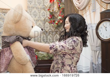 Full Asian Woman Holding And Kissing A Big Teddy Bear.