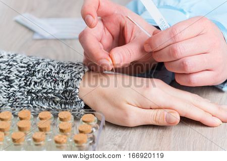 Acupuncture therapist applying acupuncture needle to her client's hand poster