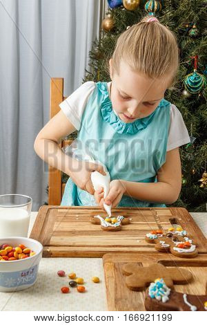 Little girl decorating of christmas gingerbread cookie near christmass tree