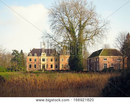 Ancient medieval stone fortress, autumn look through the grass field, castle Ruurlo, Netherlands, Europe