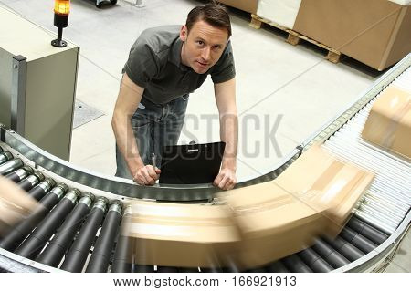 a warehouse worker standing next to a conveyor belt with moving boxes.
