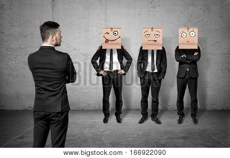 Businessman on grey concrete background turned back and looking at three men wearing carton boxes on their heads. Business communication. Corporate culture. Fitting in.