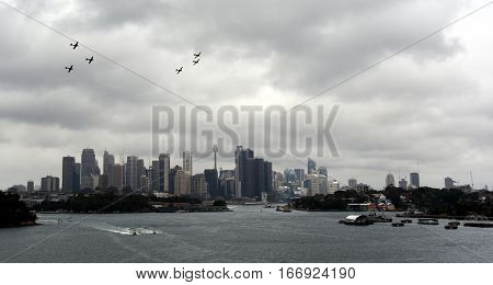Sydney Australia - January 26 2017. Synchronised aerobatic movements by the Russian Roolettes a six ship civilian formation team in Australia. Sydney city view on Australia Day from Manns Point.