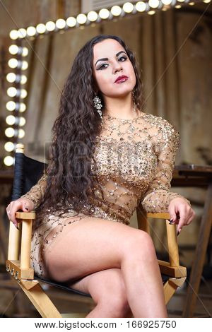 Beautiful woman with long curly hair in a short dress with sequins sitting cross-legged on a chair in front of the mirror in the dressing room