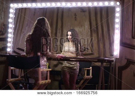 Actress in a shiny short dress looks in a large makeup room mirror with lights around the perimeter