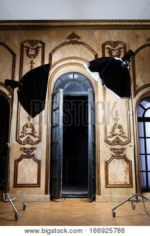 Two light source in front of the open glass doors in an ancient palace interior