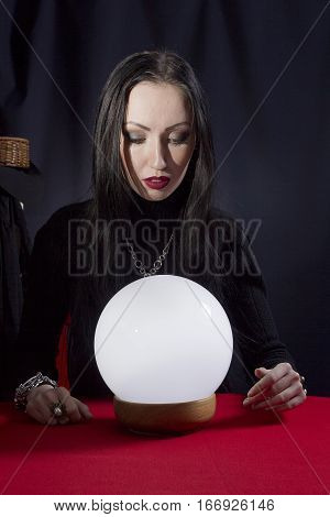 Fortune teller with a magic ball on a black background