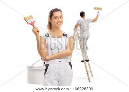 Female painter holding a color bucket and a paintbrush with a male painter painting climbed up a ladder isolated on white background