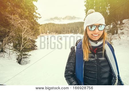 Winter clothing. Smiling woman on a skiing vacation. A smiling beautiful young woman with sunglasses and woolen hat. Winter landscape with snow, mountains and forest.