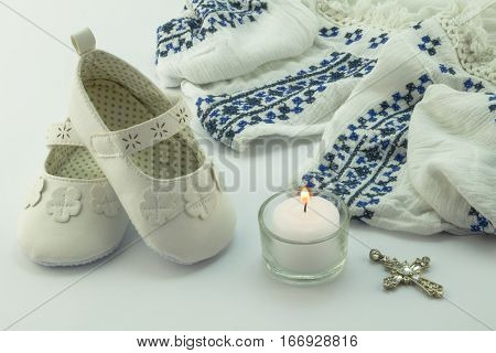 Baptism dress bootiescross and candle on white background