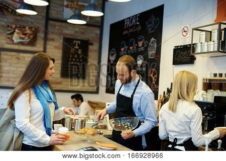 Waiter standing behind counter, serving female guest in cafeteria.