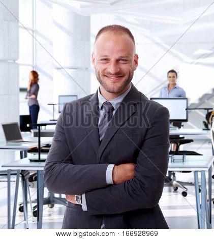 Portrait of successful caucasian business expert at office. Standing, smiling, confident, arms crossed, looking at camera.
