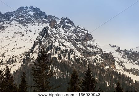 Mountain rocky landscape with fir wood forest and snow. Ortisei, Italy. Mountains of South Tyrol in northern Italy. Landscape with sky, fog, snow-capped mountains, forests of fir trees, and snow. Ortisei, Italy