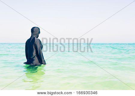 young woman in burkini swimming in the sea, persian gulf, jumeirah beach in dubai