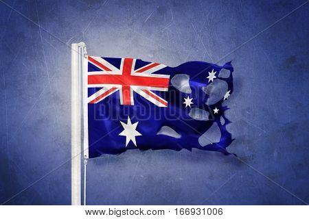 Torn flag of Australia flying against grunge background