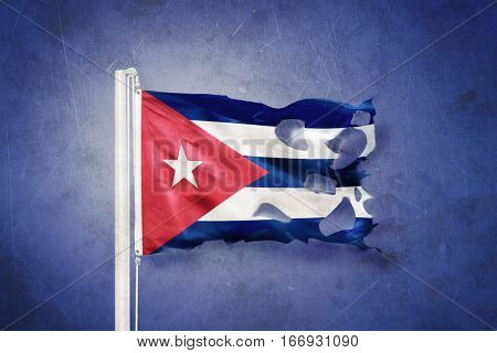 Torn flag of Cuba flying against grunge background
