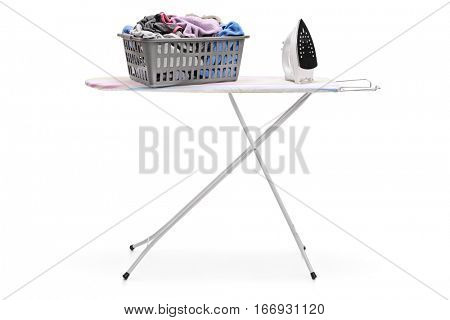 Laundry basket full of clothes and an iron on an ironing board isolated on white background