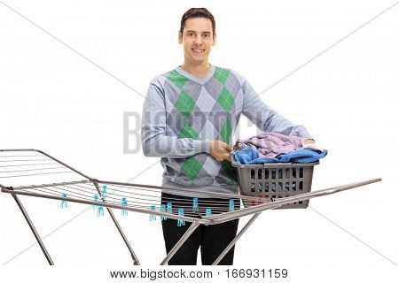 Young man holding a laundry basket full of clothes behind a clothing rack dryer isolated on white background