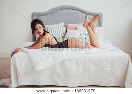 Beautiful sexy woman wearing seductive black lingerie posing in bedroom. Professional make-up and hairstyle. Perfect body and skin. Fashion photo. Natural beauty.