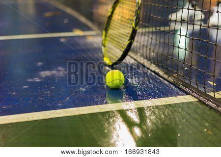 Tennis Ball, Racquet And Net On Wet Ground After Raining