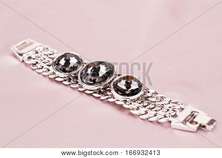 Stylish bracelet with stones on fabric background.