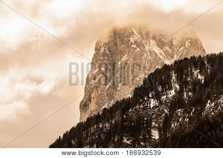 Mountains with clouds and bad weather. Rocky Mountain. Beautiful and winter mountain landscape. Mountains of South Tyrol in northern Italy. Ortisei. Landscape with cloudy sky, forests of fir trees, and snow.
