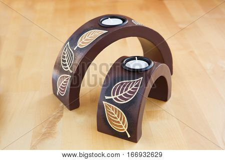 Two brown candle nests on wooden background.